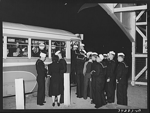 Military personnel boarding bus